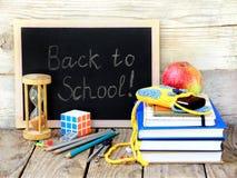 Fuentes de escuela, manzanas, libro y de nuevo a la escuela escrita Fotos de archivo libres de regalías