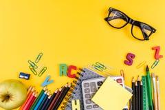 Fuentes de escuela y lentes en fondo amarillo Foto de archivo libre de regalías
