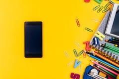 Fuentes de escuela y teléfono móvil en fondo amarillo Imagen de archivo libre de regalías