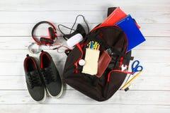 Fuentes de la mochila de la escuela y una tableta con los auriculares Fotos de archivo libres de regalías