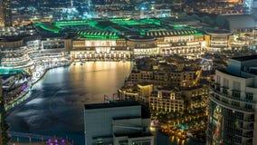 Fuentes del baile de la opinión aérea de la noche céntricas y en un timelapse del lago artificial en Dubai, UAE metrajes