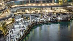 Fuentes del baile de la opinión aérea de la noche céntricas y en un timelapse del lago artificial en Dubai, UAE almacen de video