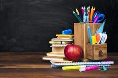 Fuentes y accesorios de escuela en la tabla de madera sobre fondo de la pizarra Foto de archivo