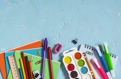 Fuentes y accesorios de escuela en un fondo azul Espacio libre para el texto Visión superior Fotografía de archivo