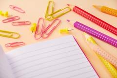 Fuentes y cuaderno de escuela en la tabla fotos de archivo