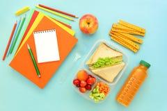 Fuentes y fiambrera de escuela con los bocadillos, los pedazos de pepinos y las zanahorias, albaricoque, cerezas, manzana, botell Fotografía de archivo libre de regalías