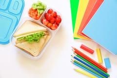 Fuentes y fiambrera de escuela con los bocadillos, los pedazos de pepinos y las zanahorias, albaricoque, cerezas, manzana, botell Fotografía de archivo