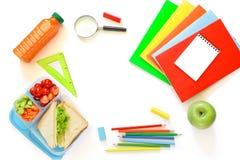 Fuentes y fiambrera de escuela con los bocadillos, los pedazos de pepinos y las zanahorias, albaricoque, cerezas, manzana, botell Foto de archivo