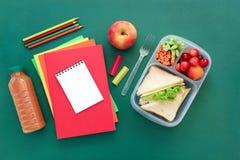 Fuentes y fiambrera de escuela con los bocadillos, los pedazos de pepinos y las zanahorias, albaricoque, cerezas, manzana, botell Imagen de archivo libre de regalías
