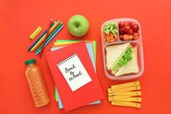 Fuentes y fiambrera de escuela con los bocadillos, los pedazos de pepinos y las zanahorias, albaricoque, cerezas, manzana, botell Fotos de archivo libres de regalías