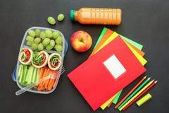 Fuentes y fiambrera de escuela con los rollos sabrosos, pepinos, zanahorias, uvas, manzana, botella de jugo en fondo negro Fotografía de archivo
