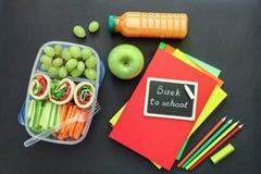 Fuentes y fiambrera de escuela con los rollos sabrosos, pepinos, zanahorias, uvas, manzana, botella de jugo en fondo negro Foto de archivo libre de regalías