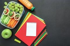 Fuentes y fiambrera de escuela con los rollos sabrosos, pepinos, zanahorias, uvas, manzana, botella de jugo en fondo negro Fotos de archivo libres de regalías
