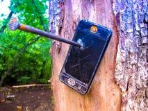 Fuera de cobertura Clavado a un árbol roto llame por teléfono fotos de archivo