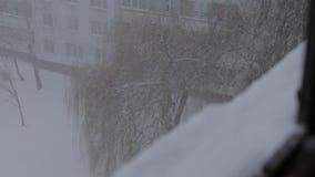 Fuera de la opinión de la ventana sobre nevada con niebla en marzo de 2019, Riga, Letonia en día ventoso almacen de video