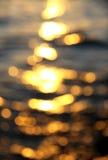 Fondo de Bokeh de la agua de mar con reflexiones del sol Imagen de archivo libre de regalías