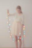 Fuera del retrato del foco de la muchacha que desempaqueta luces de la Navidad Imagenes de archivo