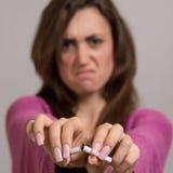 Fuera del retrato del foco de la mujer enojada que rompe un cigarrillo en dos Foto de archivo
