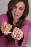 Fuera del retrato del foco de la mujer que rompe un cigarrillo en dos Imagen de archivo libre de regalías