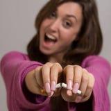Fuera del retrato del foco de la mujer que rompe un cigarrillo en dos Fotos de archivo