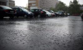 Fuertes lluvias en la calle de la ciudad con los coches parqueados en el fondo imagen de archivo