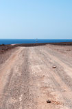 Fuerteventura, Canary Islands, Spain, dirt road, 4x4, desert, landscape, nature, climate change. The dirt road to Pozo Negro and a sailboat on August 30, 2016 Royalty Free Stock Image
