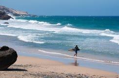 Fuerteventura, Canary Islands, Spain. A surfer on Playa de Garcey on September 6, 2016. Playa de Garcey is a black beach on the western coast where lies the royalty free stock images