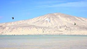 Fuerteventura - kanariefågelöar - September 2015 - Kitesurfer som går på en strand på Fuerteventura kanariefågelöar lager videofilmer