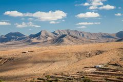 Fuerteventura landscape, Canary Islands. A yellow arid landscape with a view on some volcanoes on the barren island of Fuerteventura, one of the Canarias stock image