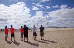 FUERTEVENTURA, SPAIN - NOVEMBER 10: A group of kite enthusiast fly their kites in formation at 31th International Kite Festival,. November 10, 2018 in Nature royalty free stock images