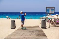 Fuerteventura Spanien 13 juni 2017: Mannen tar bilder på stranden av kanariefågelöarna Arkivbild