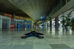 Fuerteventura, Spanje 24-maart-2019 Één kerel die op de vloer in de lege luchthaven na uitputtende vakantie liggen stock afbeeldingen