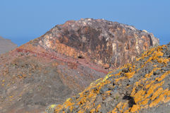 Fuerteventura stone layers 1. Rocks with Lichen yellow moss and interesting red coloured stone layers in hill peak close to the La Entallada lighthouse east of Royalty Free Stock Photography