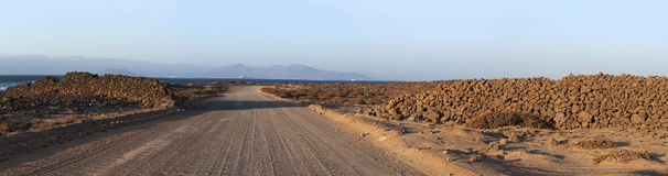 Fuerteventura, Canary Islands, Spain, desert, landscape, nature, dirt road, climate change. The dirt road from Majanicho to Corralejo at sunset with view of Royalty Free Stock Photo