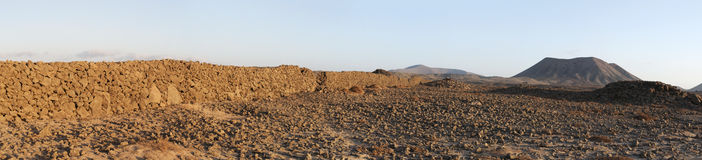 Fuerteventura, Canary Islands, Spain, desert, landscape, nature, dirt road, climate change, mountain, volcano. Stone wall and mountains at sunset on the dirt Stock Image