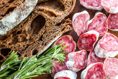 Fuet with dark-rye bread. On the wooden board Stock Photos