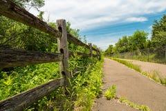 Fuga coberto de vegetação abandonada da bicicleta com a cerca de madeira rotting Foto de Stock