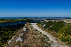A fuga de montanha de pedra conduz ao precipício contra um contexto do céu azul imagens de stock