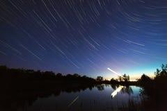 A fuga de protagoniza no c?u noturno em torno da estrela norte sobre o lago A paisagem foi fotografada com uma exposição longa no foto de stock royalty free
