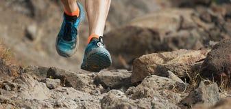 Fuga do atleta que corre nas montanhas no terreno rochoso Fotografia de Stock