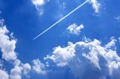 Fuga internacional do vapor do avião de passageiros acima de um céu nebuloso Foto de Stock Royalty Free