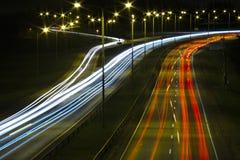 Fugas claras dos carros em uma estrada na noite foto de stock