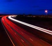 Fugas da luz do farol e da cauda na noite Foto de Stock Royalty Free