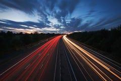 Fugas da luz em uma estrada no crepúsculo Imagem de Stock
