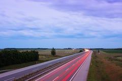 Fugas da luz na noite na estrada Imagem de Stock