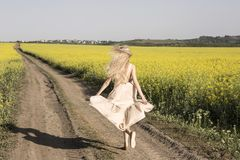 Fuggendo ragazza bionda fra i campi di fioritura di giallo Fotografie Stock Libere da Diritti