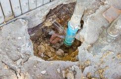 Fuites de l'eau des tuyaux bleus souterrains photographie stock