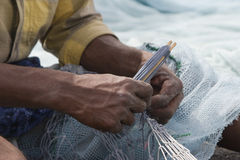 Fujairah UAE A local fisherman fixes holes and tangles in his net in Fujairah. Stock Photos