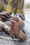 Fujairah UAE A local fisherman fixes holes and tangles in his net in Fujairah. Royalty Free Stock Images