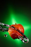 Fuji Apple Splash. A Delicoius Fuji Apple Being Splashed with Water over a Green Grandient Background Stock Photo